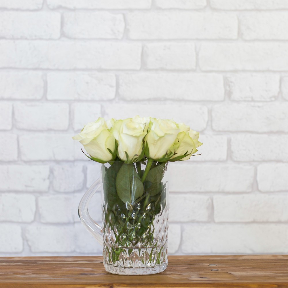 Textured clear glass water jug with flowers