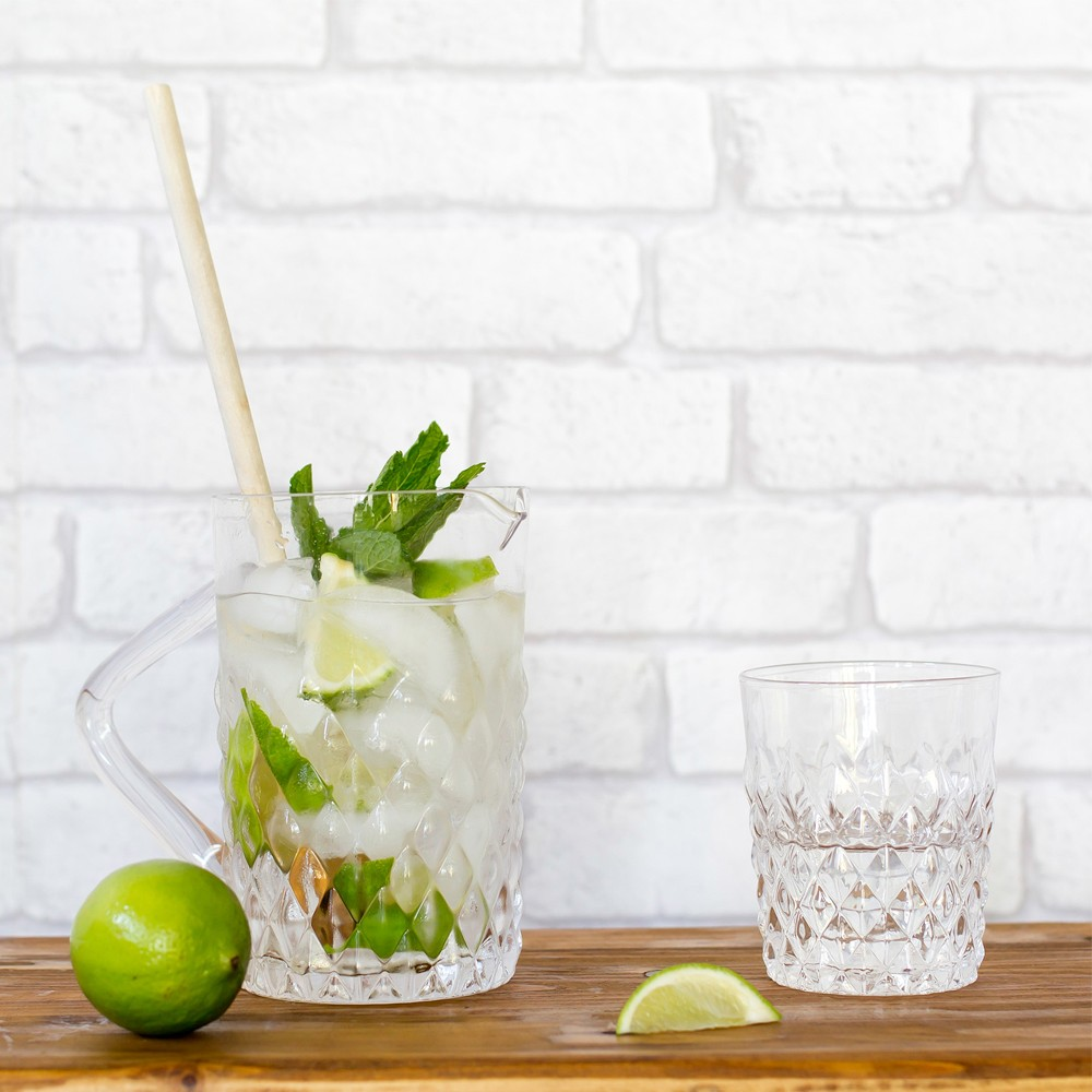 Textured clear glass water jug with limes